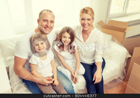 smiling parents and two little girls at new home stock photo, family, children, accommodation and home concept - smiling parents and two little girls moving into new home by Syda Productions