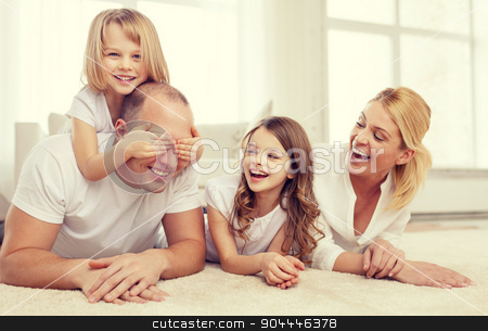 parents and two girls lying on floor at home stock photo, family, children and home concept - smiling family with and two little girls lying on floor at home and having fun by Syda Productions