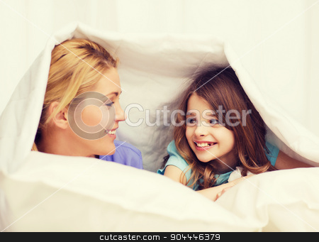 mother and little girl under blanket at home stock photo, family, child and home concept - smiling mother and little girl under blanket at home by Syda Productions