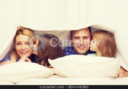 two little girls kissing their parents on cheek stock photo, family, children and home concept - two little girls kissing their parents on cheek under blanket at home by Syda Productions