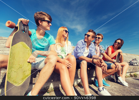 group of smiling friends sitting on city street stock photo, friendship, leisure, summer and people concept - group of smiling friends with skateboards sitting on city street by Syda Productions