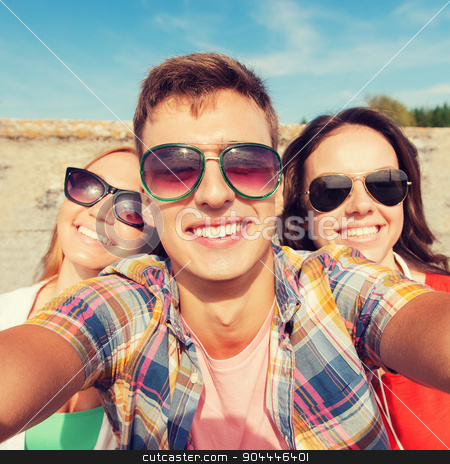 group of smiling friends taking selfie outdoors stock photo, friendship, leisure, summer, technology and people concept - group of smiling friends taking selfie outdoors by Syda Productions