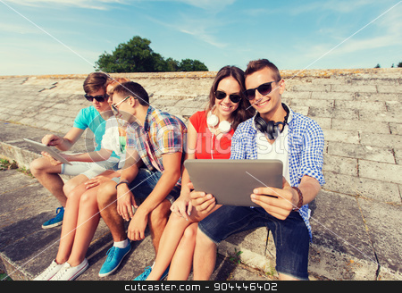 group of smiling friends with tablet pc outdoors stock photo, friendship, leisure, summer, technology and people concept - group of smiling friends with tablet pc computer and headphones sitting outdoors by Syda Productions
