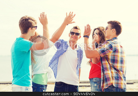 group of smiling friends making high five outdoors stock photo, friendship, leisure, summer, gesture and people concept - group of smiling friends making high five outdoors by Syda Productions