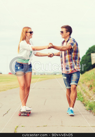 smiling couple with skateboard outdoors stock photo, holidays, vacation, love and friendship concept - smiling couple with skateboard riding and holding hands outdoors by Syda Productions