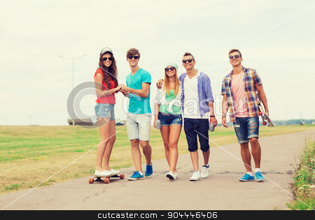 group of smiling teenagers with skateboards stock photo, holidays, vacation, love and friendship concept - group of smiling teenagers walking and riding on skateboards outdoors by Syda Productions