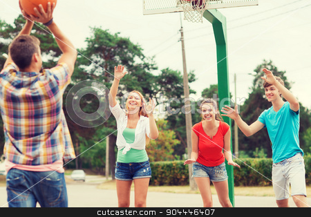 group of smiling teenagers playing basketball stock photo, summer vacation, holidays, games and friendship concept - group of smiling teenagers playing basketball outdoors by Syda Productions