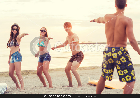 smiling friends in sunglasses with surfs on beach stock photo, friendship, sea, summer vacation, water sport and people concept - group of smiling friends wearing swimwear and sunglasses with surfboards on beach by Syda Productions