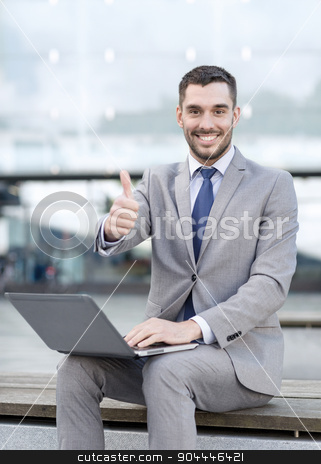 smiling businessman working with laptop outdoors stock photo, business, education, technology, gesture and people concept - smiling businessman working with laptop computer showing thumbs up on city street by Syda Productions