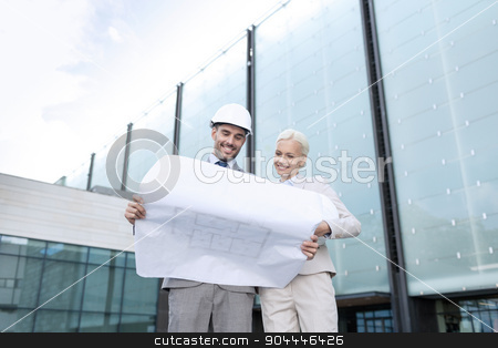 smiling businessmen with blueprint and helmets stock photo, business, partnership, architecture and people concept - smiling businessman and businesswoman with blueprint and helmets on city street by Syda Productions