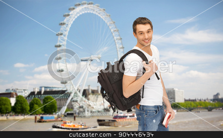 happy young man with backpack and book travelling stock photo, people, travel, tourism and education concept - happy young man with backpack and book over london ferry wheel background by Syda Productions