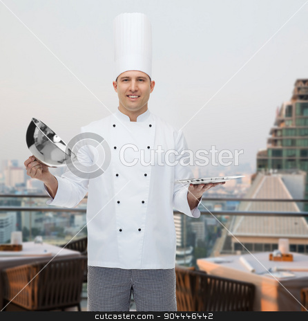 happy male chef cook opening cloche stock photo, cooking, profession and people concept - happy male chef cook opening cloche cover over city restaurant lounge background by Syda Productions