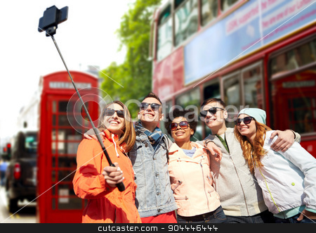 friends taking selfie with smartphone in london stock photo, tourism, travel, people, leisure and technology concept - group of smiling teenage friends taking selfie with smartphone and monopod over london city street background by Syda Productions
