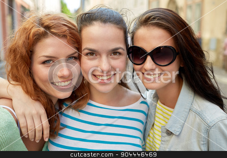 happy young women or teenage girls on city street stock photo, vacation, weekend, leisure and friendship concept - smiling happy young women or teenage girls on city street by Syda Productions