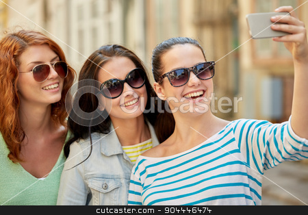 smiling young women taking selfie with smartphone stock photo, lifestyle, leisure, technology and people concept - smiling young women or teenage friends in sunglasses taking selfie with smartphone outdoors by Syda Productions
