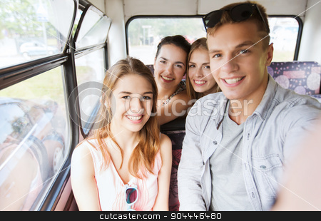 happy teenage friends traveling by bus stock photo, friendship, travel, vacation, summer and people concept - group of happy teenage friends with smartphone traveling by bus by Syda Productions