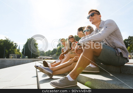 group of smiling friends sitting on city street stock photo, friendship, leisure, summer and people concept - group of smiling friends in sunglasses sitting on city street by Syda Productions