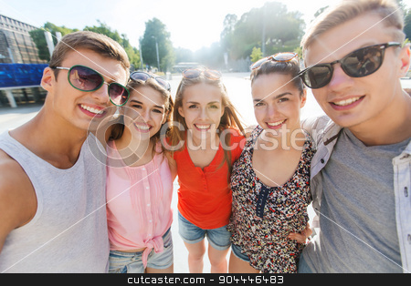smiling friends taking selfie stock photo, tourism, travel, people, leisure and technology concept - group of smiling teenage friends taking selfie outdoors by Syda Productions