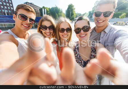 happy friends taking selfie and showing thumbs up stock photo, tourism, travel, people, leisure and technology concept - group of smiling teenage friends taking selfie and showing thumbs up outdoors by Syda Productions