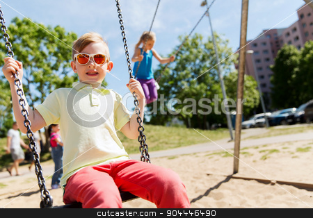 two happy kids swinging on swing at playground stock photo, summer, childhood, leisure, friendship and people concept - two happy kids swinging on swing at children playground by Syda Productions