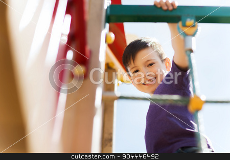 happy little boy climbing on children playground stock photo, summer, childhood, leisure and people concept - happy little boy on children playground climbing frame by Syda Productions