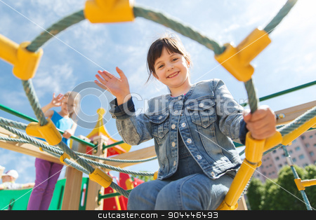 happy little girl climbing on children playground stock photo, summer, childhood, leisure, gesture and people concept - happy little girl waving hand on children playground climbing frame by Syda Productions