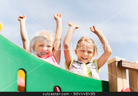 happy girls waving hands on children playground stock photo, summer, childhood, leisure, friendship and people concept - happy little girls waving hands on children playground climbing frame by Syda Productions