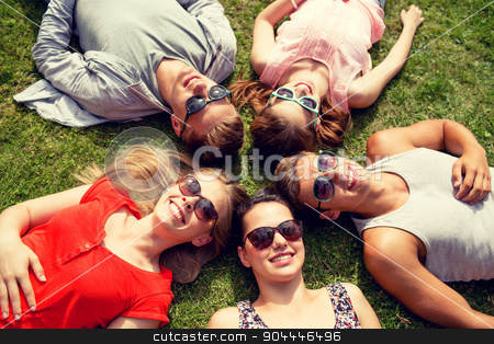 group of smiling friends lying on grass outdoors stock photo, friendship, leisure, summer and people concept - group of smiling friends lying on grass in circle outdoors by Syda Productions
