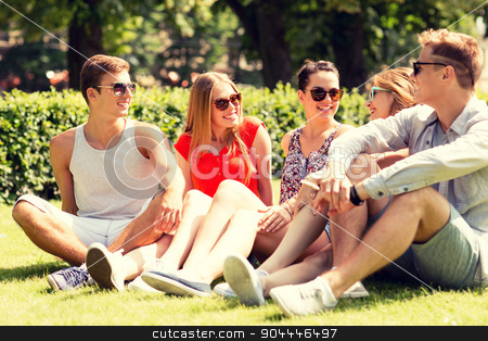 group of smiling friends outdoors sitting on grass stock photo, friendship, leisure, summer and people concept - group of smiling friends outdoors sitting on grass in park by Syda Productions