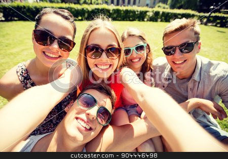 group of smiling friends making selfie in park stock photo, friendship, leisure, summer, technology and people concept - group of smiling friends making selfie with smartphone, camera or tablet pc in park by Syda Productions
