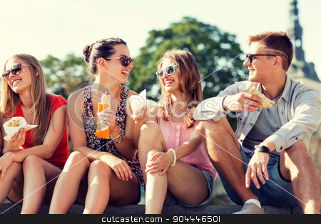 group of smiling friends sitting on city square stock photo, friendship, leisure, summer and people concept - group of smiling friends in sunglasses sitting with food on city square by Syda Productions