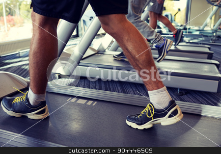 close up of men legs walking on treadmills in gym stock photo, sport, fitness, lifestyle, technology and people concept - close up of men legs walking on treadmills in gym by Syda Productions