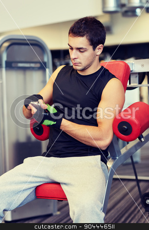 young man with smartphone in gym stock photo, sport, bodybuilding, lifestyle, technology and people concept - young man with smartphone in gym by Syda Productions