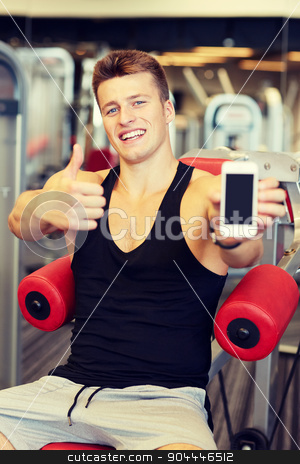smiling young man with smartphone in gym stock photo, sport, bodybuilding, lifestyle, technology and people concept - smiling young man showing smartphone and thumbs up gesture in gym by Syda Productions