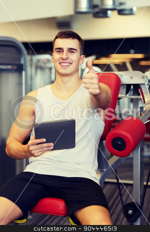 smiling young man with tablet pc computer in gym stock photo, sport, bodybuilding, lifestyle, technology and people concept - smiling young man with tablet pc computer in gym by Syda Productions