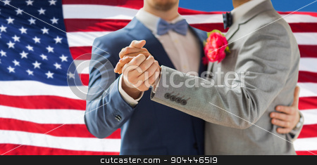 close up of happy male gay couple dancing stock photo, people, homosexuality, same-sex marriage and love concept - close up of happy male gay couple holding hands and dancing on wedding over american flag background by Syda Productions