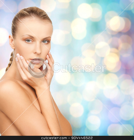 beautiful young woman touching her face stock photo, beauty, people and body care concept - beautiful young woman touching her face over blue holidays lights background by Syda Productions