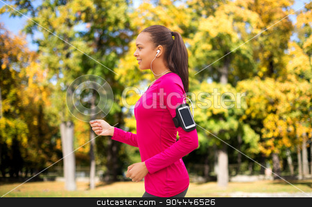 girl with smartphone and earphones running at park stock photo, sport, fitness, technology and people concept - smiling young african american woman running with smartphone and earphones over autumn park background by Syda Productions
