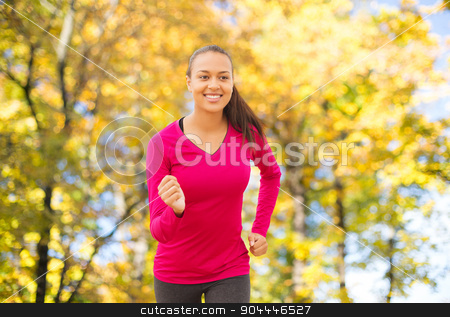 smiling woman running outdoors at autumn stock photo, fitness, sport, training and people concept - smiling african american woman running outdoors over autumn trees background by Syda Productions