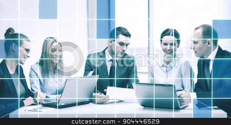 business team with laptop having discussion stock photo, business, technology and people concept - smiling business team with laptop computers, documents and coffee having discussion in office over blue squared grid background by Syda Productions