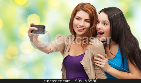 happy teenage girls taking selfie with smartphone stock photo, technology, friendship and people concept - two smiling teenage girls or young women taking selfie with smartphone over green lights background by Syda Productions