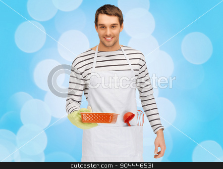 happy man or cook with baking and kitchenware stock photo, people, cooking, culinary and food concept - happy man or cook in apron with baking and kitchenware over blue lights background by Syda Productions