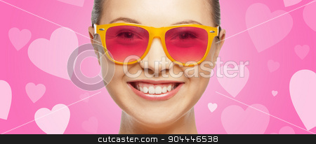 smiling teenage girl in pink sunglasses stock photo, love, happiness, valentines day, face expressions and people concept - portrait of smiling teenage girl in pink sunglasses over background with hearts by Syda Productions