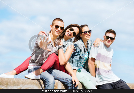 group of teenagers hanging out stock photo, summer holidays and teenage concept - group of teenagers hanging outside by Syda Productions