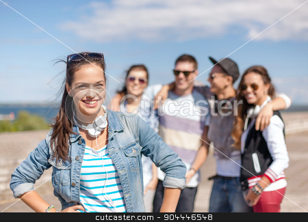 teenage girl with headphones and friends outside stock photo, summer holidays and teenage concept - teenage girl in sunglasses and headphones hanging out with friends outside by Syda Productions