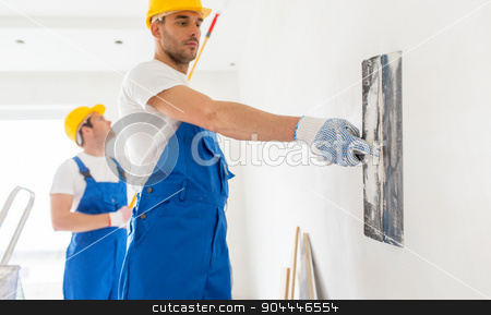 two builders with painting tools repairing room stock photo, building, repair, teamwork and people concept - two builders in hardhats and overalls with spatula and painting roller repairing room by Syda Productions