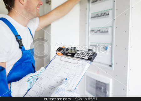 builders with clipboard and electrical panel stock photo, building, electricity, teamwork and people concept - close up of builders with clipboard and electrical panel indoors by Syda Productions
