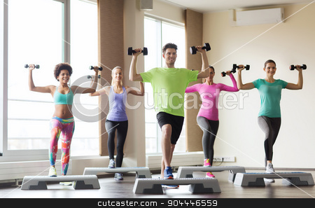 group of people with dumbbells and steppers stock photo, fitness, sport, aerobics and people concept - group of smiling people working out with dumbbells flexing muscles on step platforms in gym by Syda Productions