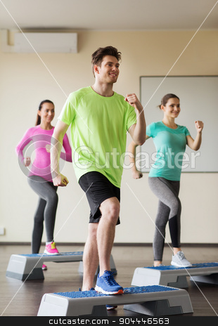 group of people working out with steppers in gym stock photo, fitness, sport, training, aerobics and people concept - group of people working out with steppers in gym by Syda Productions