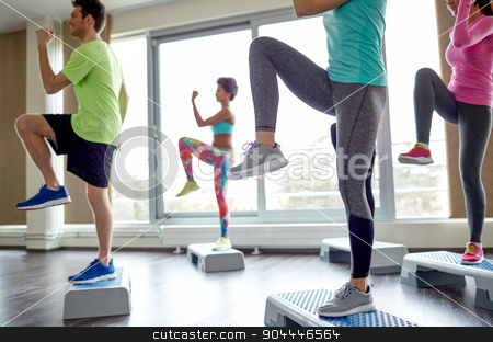 group of people raising legs on step platforms stock photo, fitness, sport, aerobics and people concept - group of smiling people working out and raising legs on step platforms in gym by Syda Productions